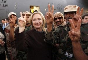 REFILE - CORRECTING COUNTRY AT END OF CAPTION U.S. Secretary of State Hillary Clinton (C) gestures with Libyan soldiers upon her departure from Tripoli in Libya October 18, 2011.  REUTERS/Kevin Lamarque  (LIBYA - Tags: POLITICS)