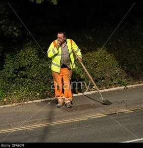 DFA60R A local authority council direct labour worker leaning on his spade shovel smoking a cigarette UK